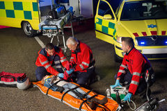 Paramedics helping motorbike driver on stretcher royalty free stock images