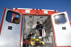 Paramedics with man on stretcher in ambulance, low angle view. Paramedics with men on stretcher in ambulance, low angle view Royalty Free Stock Image