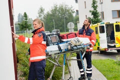 Paramedics with medical equipment ringing doorbell. Ambulance house call aid stock photography