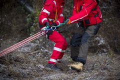 Paramedics mountain rescue service. Paramedics from mountain rescue service provide first aid during a training for saving a person in accident in the forest royalty free stock photo