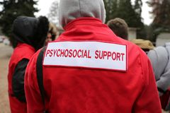 Paramedics mountain rescue service Psychosocial Support. Paramedics from mountain rescue service provide first aid during a training for saving a person in royalty free stock image