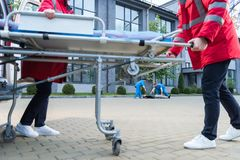 Paramedics moving ambulance stretcher to. Injured man royalty free stock images