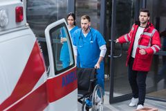 paramedics moving wheelchair from hospital stock images