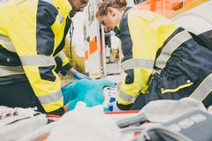 Paramedics performing first aid at ambulance. Helping a woman royalty free stock images