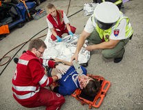 Paramedics stabilizing the patient. Policeman makes the breath t Royalty Free Stock Images