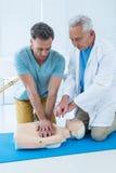 Paramedics training cardiopulmonary resuscitation to man stock photos