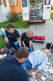 Paramedics treating injured man on street Stock Image