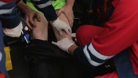 Paramedics urgently examining patient legs and knees, suspicion of bones injury. Stock footage stock video