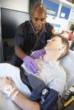 Paramedicus die bij patiënt in ziekenwagen aanwezig is royalty-vrije stock foto's