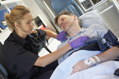 Paramedicus die bij patiënt in ziekenwagen aanwezig is Royalty-vrije Stock Foto