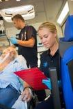 Paramedicus die verwonde patiënt bijstaan in ziekenwagen royalty-vrije stock foto's