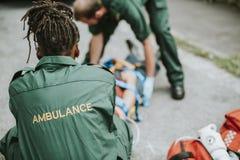 Paramedicusteam die een verwonde patiënt redden stock fotografie
