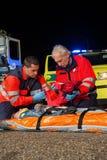 Paramedicusteam die eerste hulp geven aan verwonde vrouw Royalty-vrije Stock Fotografie