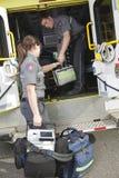 Paramedicuswerknemer met ziekenwagen in stock foto
