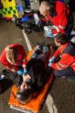 Paramedizinisches Team, das verletztem Motorradfahrer hilft Lizenzfreies Stockfoto