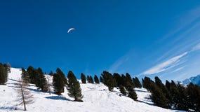 Paramilitar no céu sobre a inclinação de montanha Fotos de Stock Royalty Free