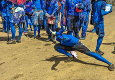 A Paramin Blue Devil strikes a pose as he celebrates Carnival in Trinidad. A Paramin Blue Devil accompanied by a bunch of young men painted in blue with plastic Royalty Free Stock Photos