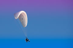 Paramotor in a colorful sky. A paramotor flying against a blue-violet sky, shoot in Cadiz, Spain Royalty Free Stock Image