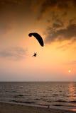 Paramotor de silhouette dans le coucher du soleil avec la vue de mer Photographie stock