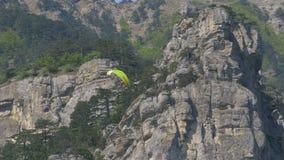Paramotor-Fliegen Fallschirmspringer mit dem Motor fliegt gegen den Hintergrund der Berge stock video