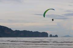 Paramotor flyger över stranden arkivfoto