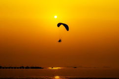 Paramotor flying on sunset background Stock Photo