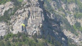 Paramotor het vliegen Parachutist met de motorvliegen tegen de achtergrond van de bergen stock videobeelden