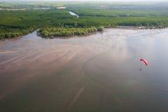 鸟瞰图、红色滑翔伞或者paramotor飞行在海,绿色美洲红树海岛背景 帽子晁Mai国家公园 Trang 免版税图库摄影
