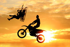 Paramotor and motocross  jump competition. Paramotor and motocross  jump  competition on sunset background Stock Image