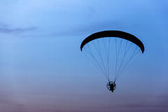 paramotor / paraglider flying into morning sky, Silhouette photo Stock Photo
