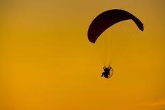 Paramotor-Schattenbild-Sonnenuntergang-orange Licht-bewölkter Hintergrund Stockfoto