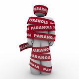 Paranoia Word Man Wrapped Tape Anxious Stress Worry. Man wrapped in red tape with Paranoia word as someone who is worried, anxious, stressed out or afraid of Stock Photo