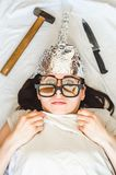 Paranoid girl wears foil hat and sleeps with weapon and different glasses because of mental disorder. Concept of fears of aliens fbi or radiation stock image