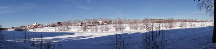Paranoma winter landscape. Village near the forest in winter in the snow. Sunny frosty day.  royalty free stock images