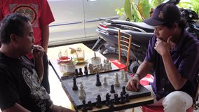 Parapat, Sumatra Indonesia - 23 JUNE 2016: Local men playing chess. Asian men playing chess outdoors stock video footage