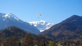 Parapendio con il parco di Interlaken del fondo della montagna della neve Immagini Stock Libere da Diritti
