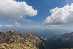 Parapendio nelle montagne svizzere con cielo blu e le nuvole Fotografia Stock