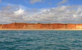 Parapendio sopra Cliff By variopinto una spiaggia Immagine Stock
