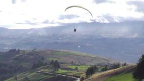 Parapendio in tandem che sorvola zona rurale nelle Ande stock footage