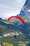 Parapente dans les Alpes suisses Photographie stock libre de droits