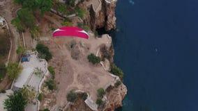 Parapente sobre a opinião superior aérea do mar e das rochas vídeos de arquivo