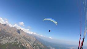 Parapente sobre os cumes em um dia de mola bonito, Itália video estoque