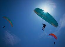 Parapentes montant dans un ciel bleu photo stock
