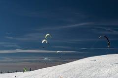 Parapentisme avec des surfs des neiges image libre de droits