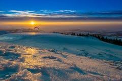 Parapentisme dans le coucher du soleil Photo stock