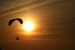 Parapentiste au-dessus de la mer au coucher du soleil Image stock