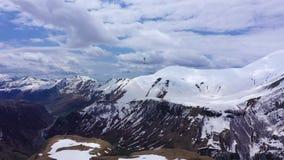 Parapentiste parmi les montagnes couronnées de neige du Caucase banque de vidéos