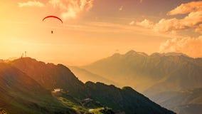 Parapentiste rouge dans le ciel nuageux de coucher du soleil orange au-dessus des montagnes vertes Vallée verte avec le funiculai photos stock