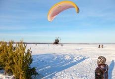 Parapentiste volant à basse altitude au-dessus de rivière neigeuse Image libre de droits