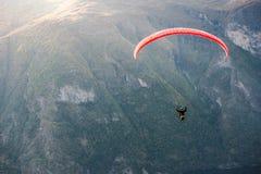 Parapentiste volant au-dessus d'Aurlandfjord, Norvège Photographie stock libre de droits